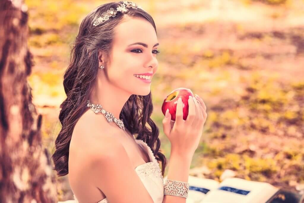 quinceañera sentada en el bosque sujetando una manzanae